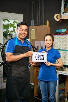 Positieve jonge mensen die een teken houden om een fietsworkshop te openen en naar de camera glimlachen