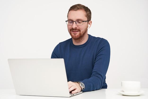 Positieve jonge mooie bebaarde man met oortelefoons die de handen op het toetsenbord houden en graag lacht tijdens het typen van tekst, geïsoleerd tegen een witte achtergrond