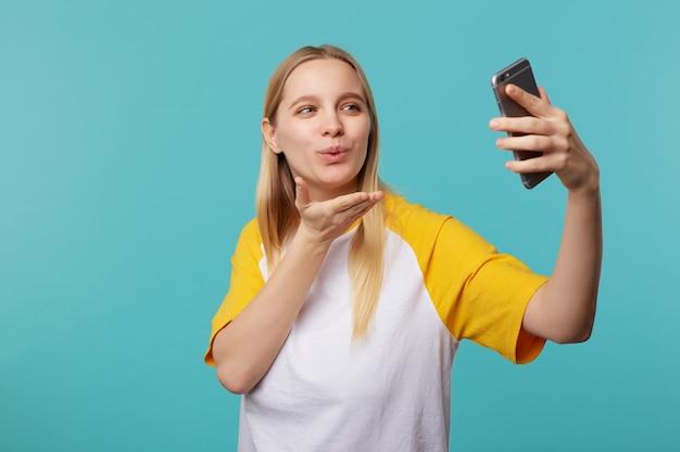 Positieve jonge mooie blonde langharige dame met natuurlijke make-up waait luchtkus tijdens het maken van portret van zichzelf, geïsoleerd op blauw