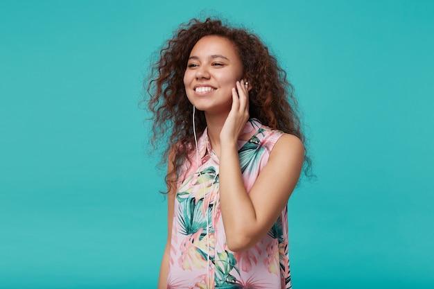 Positieve jonge mooie bruinharige krullende dame met casual kapsel houden opgeheven hand op oortje en mooi glimlachend terwijl je geniet van favoriete muzieknummer, geïsoleerd op blauw