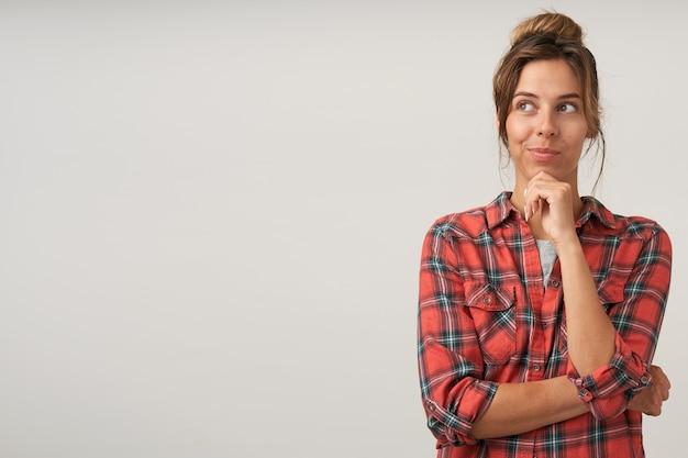 Positieve jonge mooie bruinharige vrouw met broodje kapsel glimlachend lichtjes terwijl opzij kijken en houden opgeheven hand op haar kin, geïsoleerd op witte achtergrond