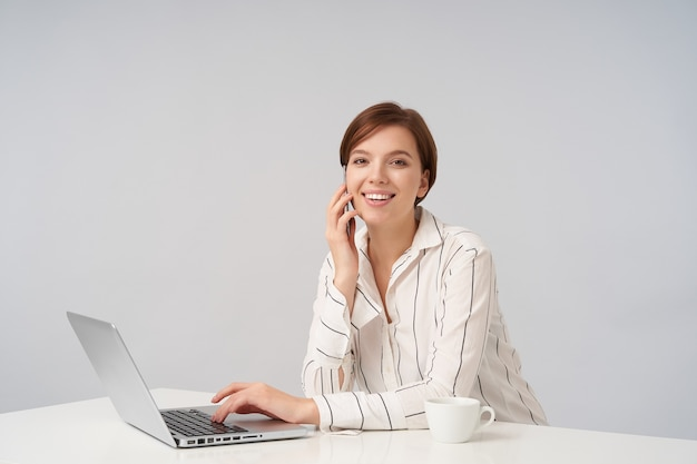 Positieve jonge mooie bruinogige brunette zakenvrouw bellen met haar smartphone en hand houden op toetsenbord van laptop terwijl vrolijk kijken