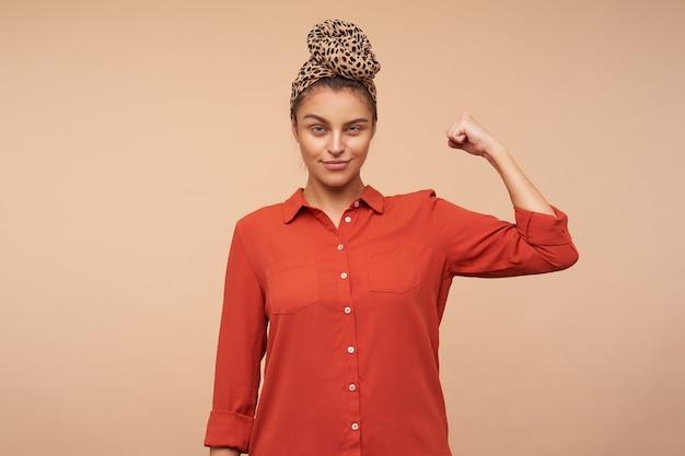 Positieve jonge mooie brunette vrouw met natuurlijke make-up met haar ogen dichtgeknepen terwijl ze naar de voorkant kijkt en de hand omhoog houdt, poseren over beige muur