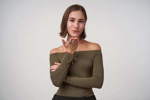 Positieve jonge mooie donkerharige dame met kort kapsel die haar handpalm omhoog houdt terwijl ze een luchtkus naar voren blaast, een olijfkleurige blouse draagt terwijl ze over een witte muur staat