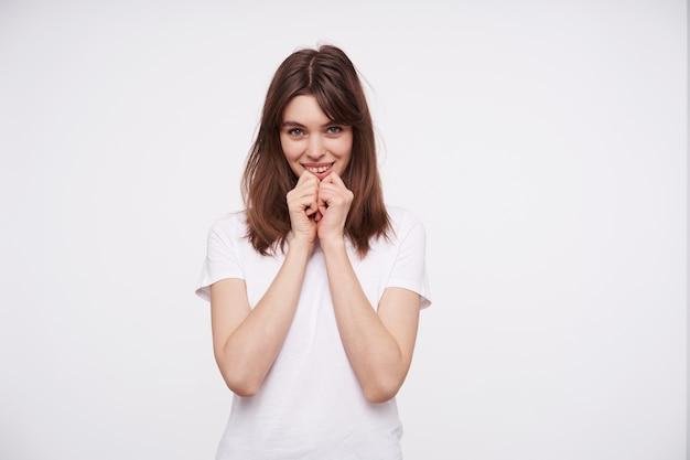 Positieve jonge mooie donkerharige dame met natuurlijke make-up die opgeheven handen onder haar kin houdt en zacht glimlacht terwijl ze graag kijkt, geïsoleerd over witte muur