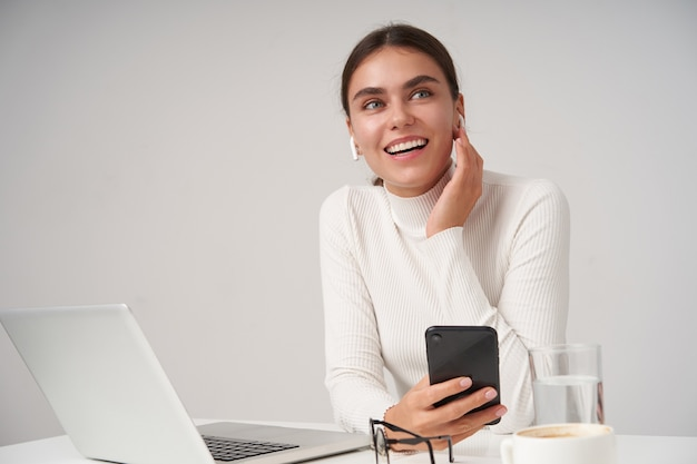 Positieve jonge mooie donkerharige vrouw met natuurlijke make-up die opgeheven hand op oortje houdt en vrolijk opzij kijkt met mobiele telefoon in haar hand, geïsoleerd over witte muur