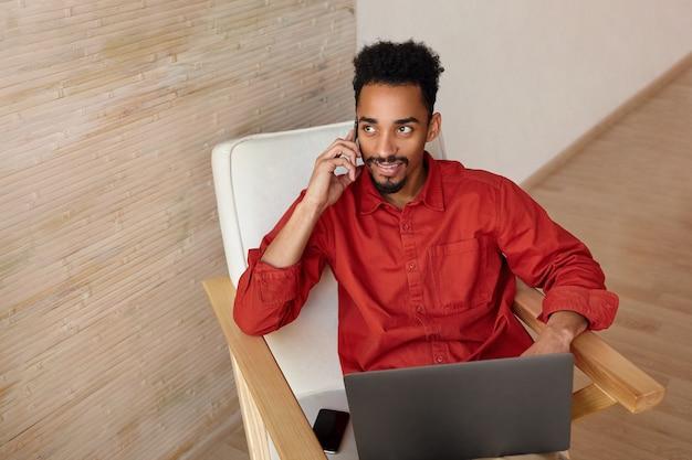 Positieve jonge mooie kortharige bebaarde man met donkere bellen met zijn smartphone tijdens het werken op afstand vanuit huis, geïsoleerd op beige interieur