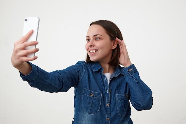 Positieve jonge mooie kortharige brunette dame mooi glimlachend terwijl het maken van foto van zichzelf, gekleed in wit t-shirt en spijkerbroek jas terwijl poseren op witte achtergrond