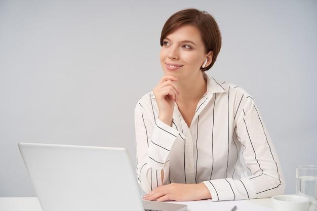 Positieve jonge mooie kortharige brunette vrouw houdt opgeheven hand op haar kin terwijl ze dromerig opzij kijkt en aangenaam lacht, zittend op wit in formele kleding