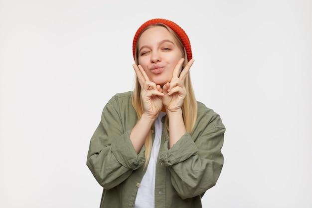 Positieve jonge mooie langharige blonde dame die haar lippen nastreeft en vredesgebaar met opgeheven handen toont terwijl ze tegen blauw in rode hoed staat