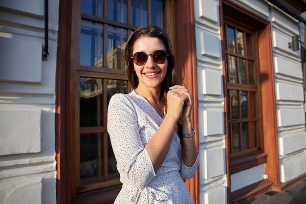 Positieve jonge mooie langharige brunette dame in zonnebril opgeheven handen vouwen en vrolijk glimlachen