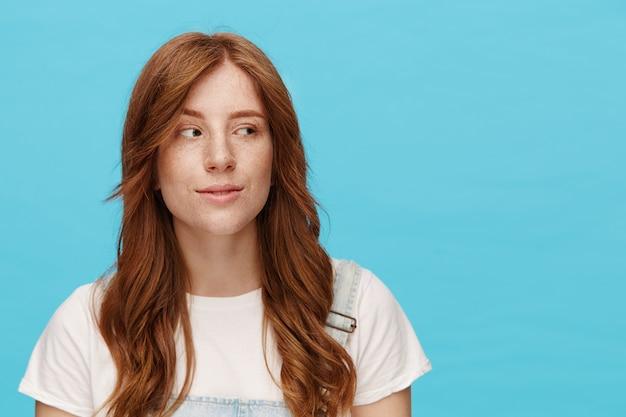 Positieve jonge mooie roodharige dame met natuurlijke make-up die sluw opzij kijkt terwijl ze iets plot, vrijetijdskleding draagt terwijl ze over een blauwe achtergrond staat