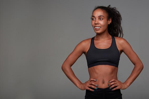Positieve jonge mooie sportieve vrouw met donkere huid en lang bruin krullend haar die vrolijk opzij kijkt en de handen op haar middel houdt, geïsoleerd in atletiekkleding