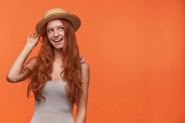 Positieve jonge mooie vrouw met golvend foxy haar poseren op oranje achtergrond, grijs shirt en schipper hoed dragen, vrolijk opzij kijken en hand opsteken om hoofdtooi recht te trekken