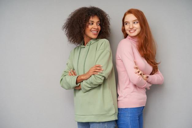 Positieve jonge mooie vrouwen die vrolijk over hun schouders naar elkaar kijken en graag glimlachen, staande over grijze muur met gekruiste handen