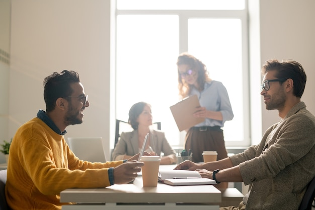 Positieve jonge multi-etnische marketingexperts zitten aan tafel in de vergaderruimte en delen ideeën terwijl ze een nieuwe reclamecampagne bespreken
