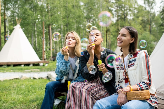 Positieve jonge multi-etnische vrouwen die bij tent in bos zitten en zeepbellen blazen