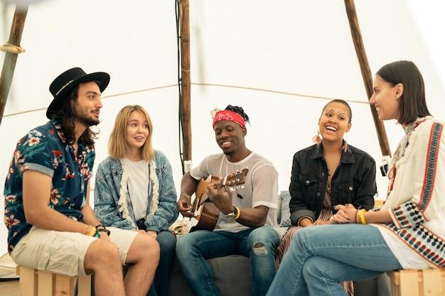 Positieve jonge sex tussen verschillendre rassen vrienden zitten in tent en luisteren naar muziek uitgevoerd door zwarte gitarist