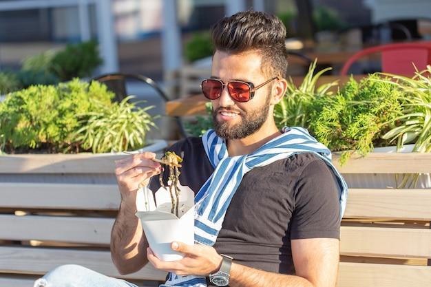 Positieve jonge stijlvolle arabische man chinese noedels eten in een park tijdens een pauze op het werk. het concept van rust en een gezonde snack.