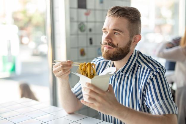 Positieve jonge stijlvolle man chinese noedels eten in een café tijdens een pauze op het werk. het concept van rust en een gezonde snack.