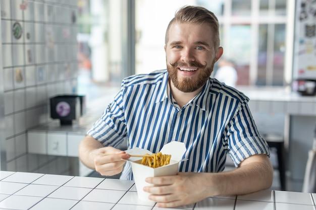 Positieve jonge stijlvolle man chinese noedels eten in een café tijdens een pauze op het werk. het concept van