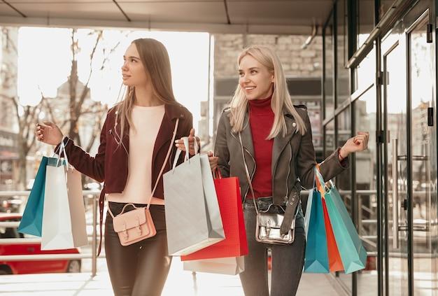 Positieve jonge stijlvolle vriendinnen in trendy outfits glimlachen tijdens het wandelen op straat met boodschappentassen stad