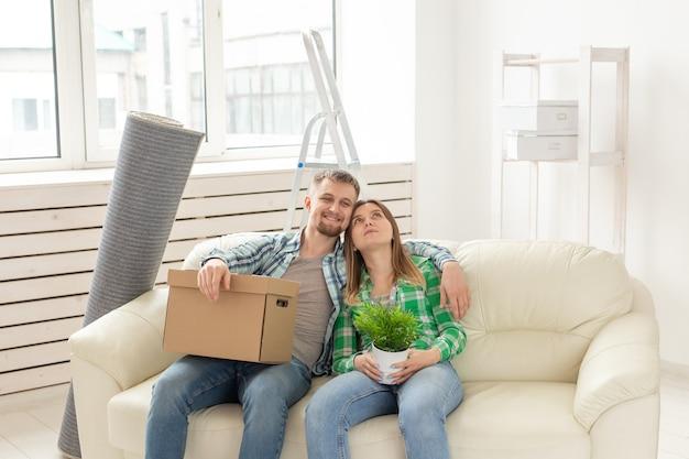 Positieve jonge verliefde man en vrouw zitten op de bank in de nieuwe woonkamer