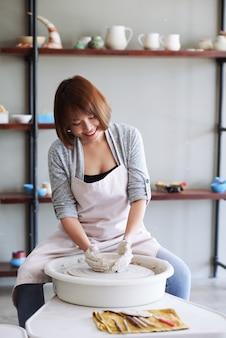 Positieve jonge vietnamese vrouwelijke keramist die kleiproduct maakt op pottenbakkerswiel in studio