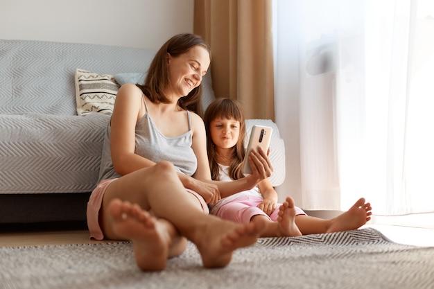 Positieve jonge volwassen blanke vrouw die casual kleding draagt die binnenshuis in de woonkamer poseert met haar dochter terwijl ze op de grond zit in de buurt van de bank en het raam, grappige video kijkend met kind.