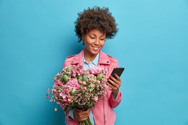 Positieve jonge vrouw accepteert gefeliciteerd met haar verjaardag houdt mobiele telefoon boeket bloemen draagt roze jas geïsoleerd over blauwe muur controleert newsfeed