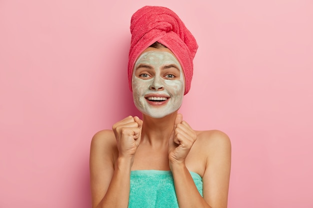 Positieve jonge vrouw balt vuisten van vreugde, past kleimasker toe op gezicht, draagt een roze handdoek op het hoofd, wil natuurlijke schoonheid hebben, modelleert binnen, glimlacht breed, drukt geluk uit. welzijn
