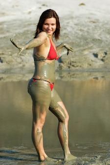 Positieve jonge vrouw besmeurd met geneeskrachtige modder uit het meer op een zonnige warme zomerdag terwijl u ontspant. gezondheid herstel concept