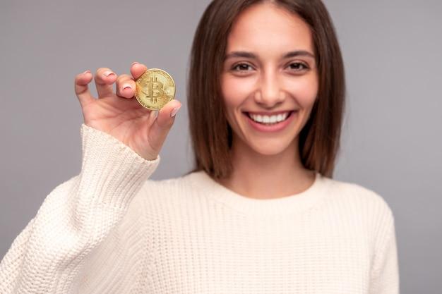 Positieve jonge vrouw bitcoin demonstreren