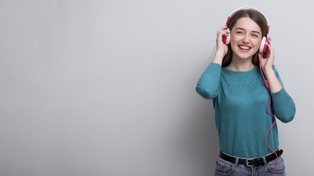 Positieve jonge vrouw die aan muziek luistert