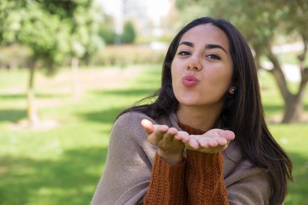 Positieve jonge vrouw die luchtkus in stadspark verzendt