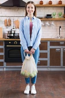 Positieve jonge vrouw die opnieuw te gebruiken zak met vruchten houdt