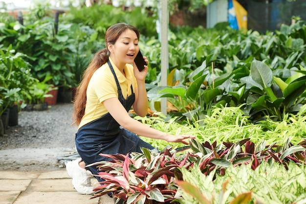 Positieve jonge vrouw die telefonisch praat met de klant die planten voorbereidt voor levering