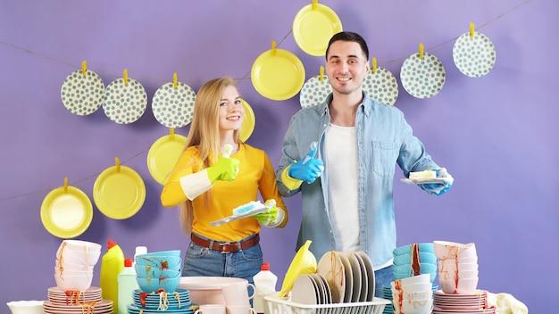 Positieve jonge vrouw en een zwartharige man geven duimen op terwijl ze schone borden vasthouden. schone platen hangen aan wasknijpers op de achtergrond