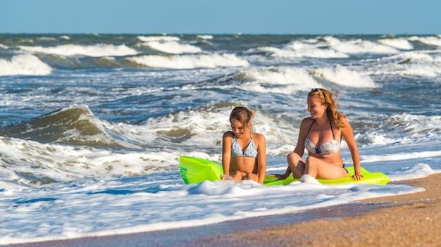 Positieve jonge vrouw en haar dochter baden in de schuimende stormachtige zeegolven op een luchtbed