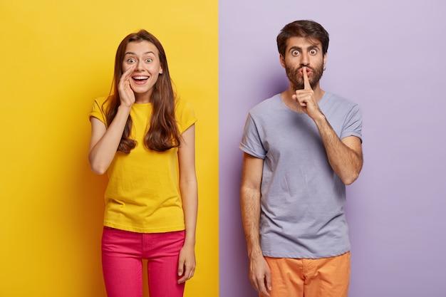Positieve jonge vrouw fluistert geheim met blije uitdrukking, serieuze man houdt de vinger op de lippen