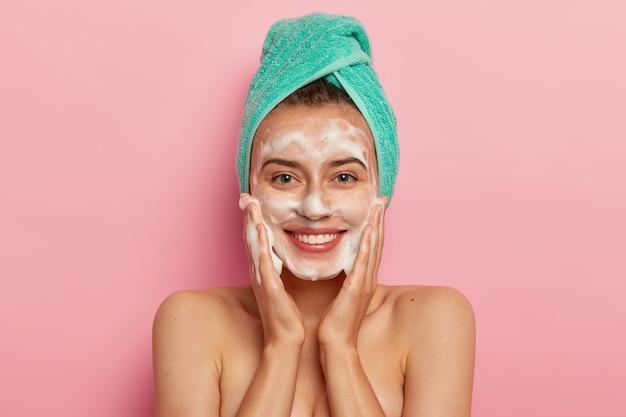 Positieve jonge vrouw heeft brede glimlach, heeft perfecte tanden, aait de huid met vloeibare hygiënische zeep, wast met schuimende gel, wordt 's ochtends wakker voor een schoonheidsroutine