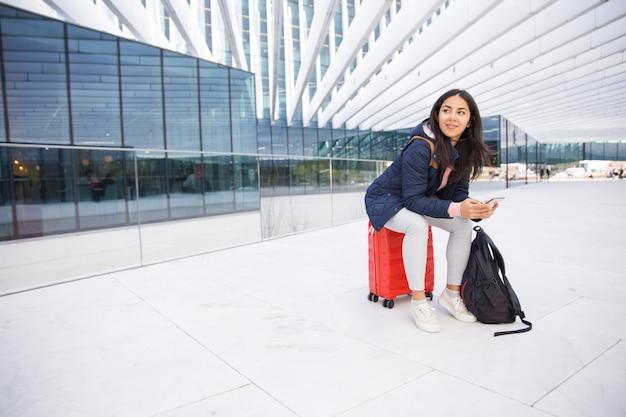 Positieve jonge vrouw in jasje die netto op smartphone surfen