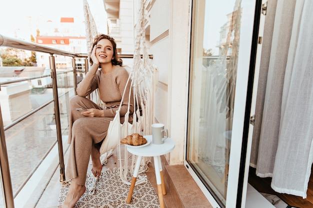 Positieve jonge vrouw in lange jurk zit op balkon met koffie en een croissant. foto van blootsvoets krullend meisje genieten van ontbijt op terras.