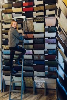 Positieve jonge vrouw kiest met verf voor reparatie huis in de winkel.