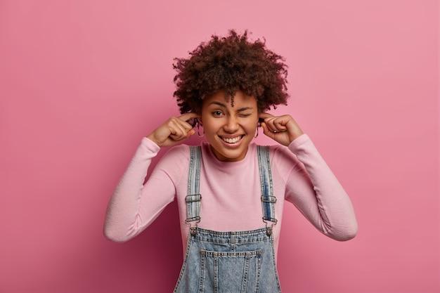 Positieve jonge vrouw met donkere huid knipoogt en sluit oren af, niet bereid om hard geluid te luisteren, komt op een luidruchtig feest, is in een goed humeur, doet alsof ze het niet hoort, geïsoleerd over een roze pastelkleurige muur