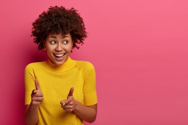 Positieve jonge vrouw met een donkere huidskleur, kiest jou, voelt zich gelukkig en ontspannen, giechelt blij, kijkt opzij, draagt een geel t-shirt, poseert tegen een roze muur, kopieer ruimte opzij
