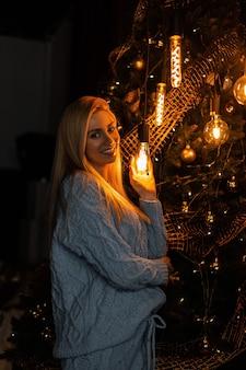 Positieve jonge vrouw met een glimlach in een trendy gebreid pak poseren in de studio in de buurt van een kerstboom met slingers met speelgoed met lampen