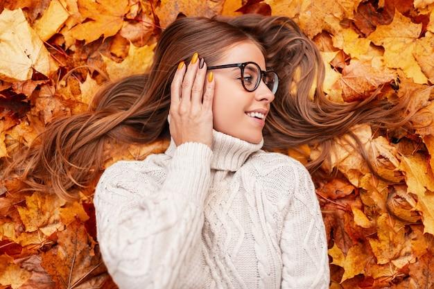 Positieve jonge vrouw met een mooie glimlach in een stijlvolle bril in een trendy witte gebreide trui rust in de herfst oranje gebladerte in het bos. vrolijk meisje ontspant buiten in een park.