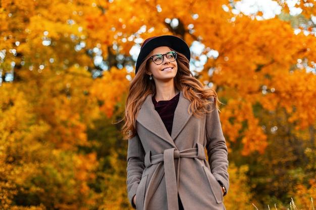 Positieve jonge vrouw met een mooie glimlach met krullend haar in een elegante hoed in een stijlvolle jas met trendy bril geniet van het weekend in het herfstpark. leuk gelukkig hipster meisje is ontspant buitenshuis.