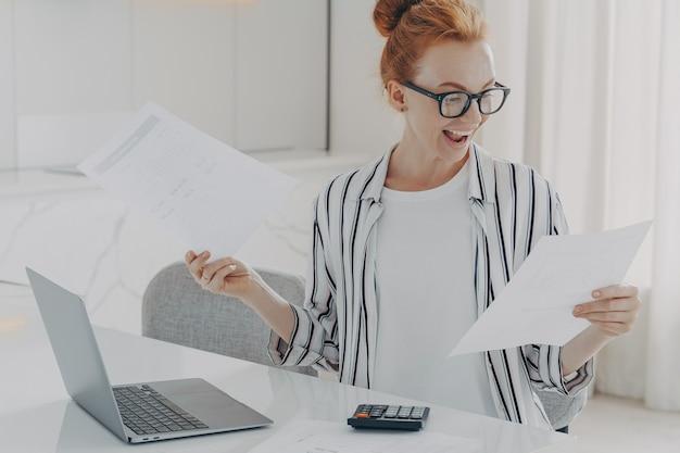 Positieve jonge vrouw met rood haar berekent de kosten van nutsvoorzieningen die betrokken zijn bij het plannen van het maandelijkse budget